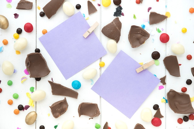 Small papers with cracked chocolate and candies on table