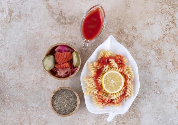Небольшая тарелка с макаронами, ломтик лимона, ассорти из солений и миска черного перца на мраморной поверхности.