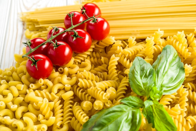 Small pasta for soups, curly pasta and basil leaf with tomatoes on the table