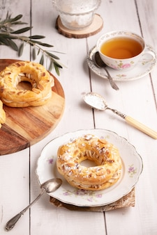 Small pastry paris brest in an old plate on a white wooden table
