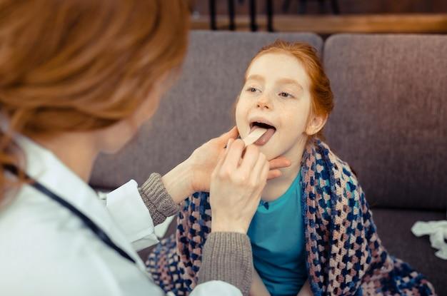 작은 환자. 그녀의 의사를 보면서 그는 입을 열고 좋은 귀여운 소녀