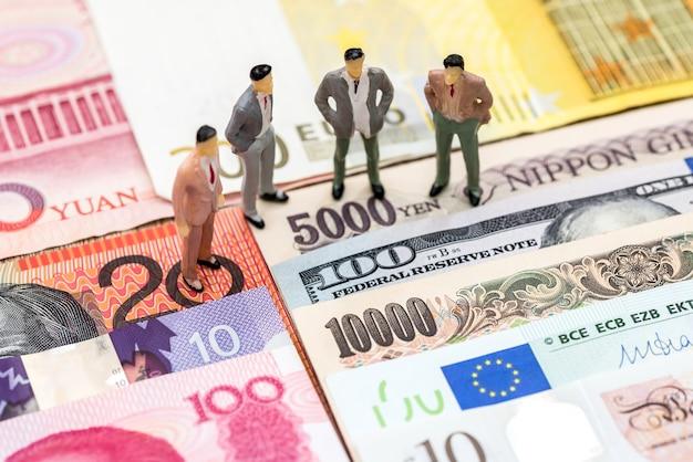 さまざまな国からのお金の背景にある小さな人々