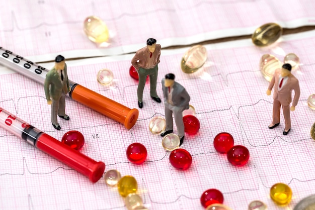 Small people with pills and cardiogram