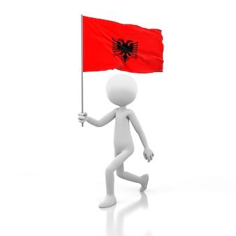손에 알베니아 깃발을 들고 걷는 작은 사람. 3d 렌더링 이미지