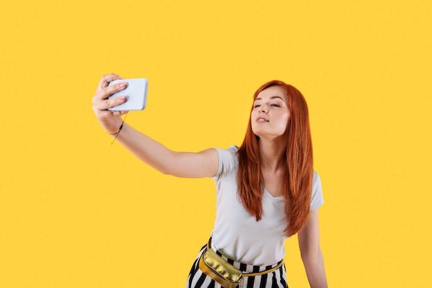 작은 사진 촬영. 그녀의 스마트 폰을 사용하는 동안 셀카를 복용 좋은 즐거운 여자