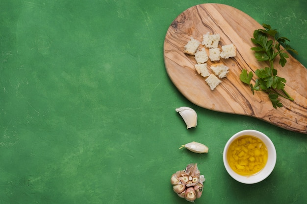 Small pieces of breads; parsley; garlic and bowl of infused olive oil on green textured background