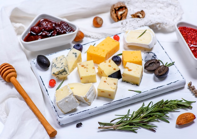 Small pieces of brie cheese, roquefort, camembert, cheddar and cheese with walnuts