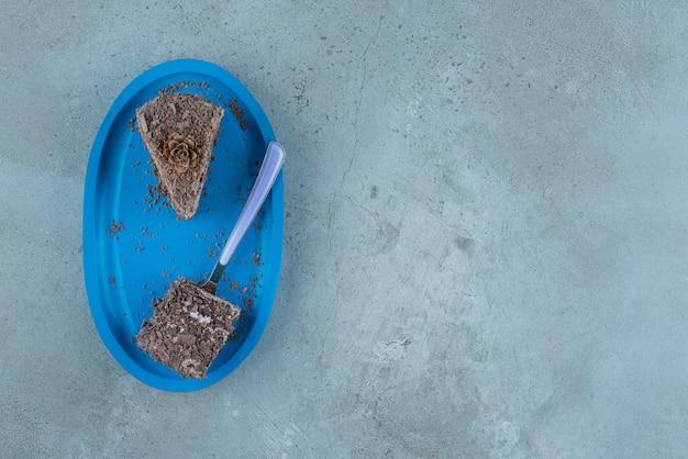 大理石の背景に青い大皿にチョコレートケーキとフォークの小片。高品質の写真