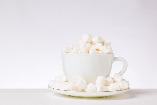 白いカップにマシュマロの小片と白いテーブルに受け皿。美味しいデザート。