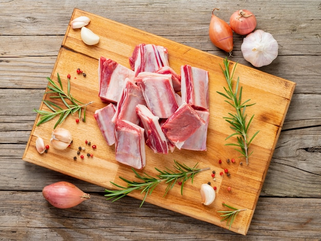 Small pieces of raw lamb ribs on wooden chopping board on old rustic wooden background