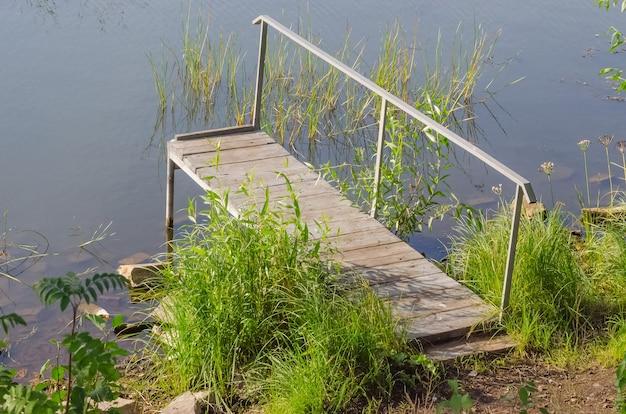 여름에 조용한 호수에 푸른 잔디와 작은 부두
