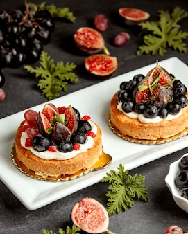Small pies decorated with figs blueberries and grapes