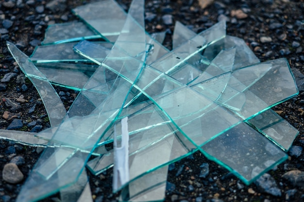 A small pile of broken glass lying on the asphalt.