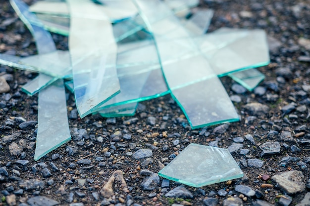 A small pile of broken glass lying on the asphalt
