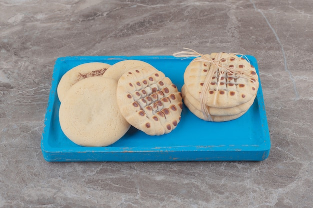 Small pile of cookies on a blue platter on marble