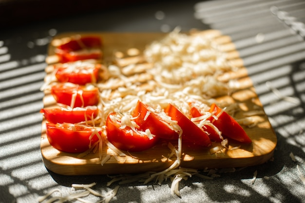 A small pile of grated fresh cheese and red tomatoes lies on a wooden board in the kitchen