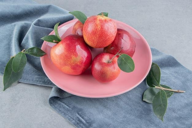 大理石の布の大皿にリンゴの小さな山。
