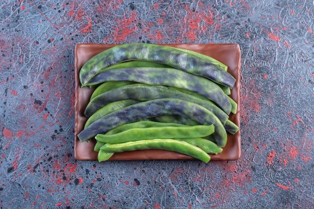 Небольшая куча бобовых бобов на блюде на темном фоне. фото высокого качества