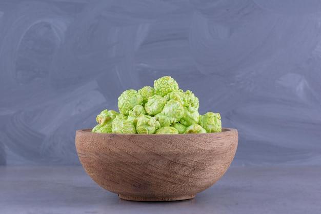 대리석 배경에 나무 그릇에 녹색 팝콘 사탕의 작은 더미. 고품질 사진