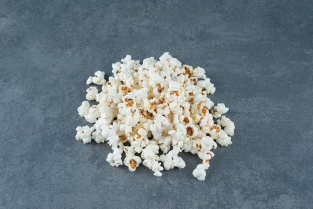 Piccolo mucchio di popcorn stuzzicanti su marmo