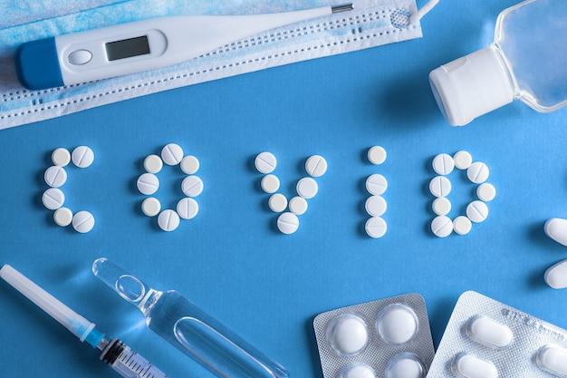 Маленькие таблетки разного цвета и формы, расположенные словом (covid - 19) на синем фоне. понятие о коронавирусе.