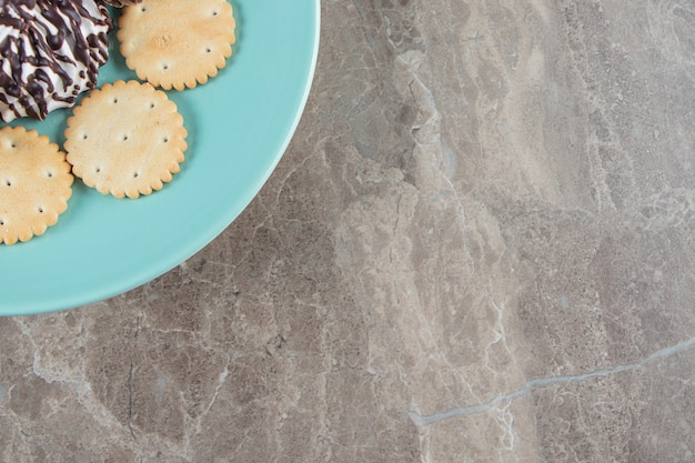 Маленькие сосны, крекер и шоколадное печенье на тарелке на синем.