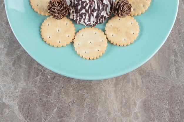 Piccoli biscotti di pino, cracker e cioccolato su un piatto da vicino sul blu.