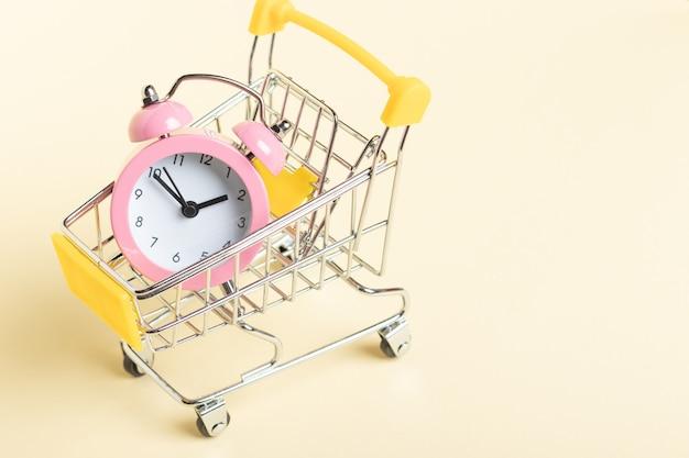 黄色の背景のショッピングカートに小さなピンクの目覚まし時計