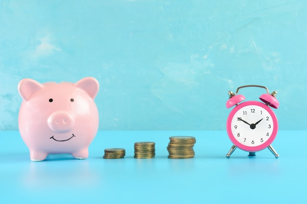 A small pink alarm clock, a stack of coins and a piggy bank on blue