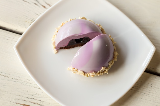 Small pink cake on plate. dessert with filling. mousse cake with blueberry jelly. glaze and cream.