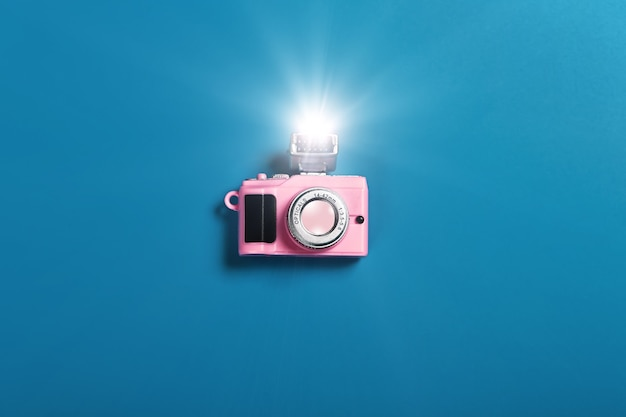 Small pink camera with flash on blue background