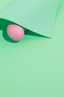 Small pink easter egg under paper on table
