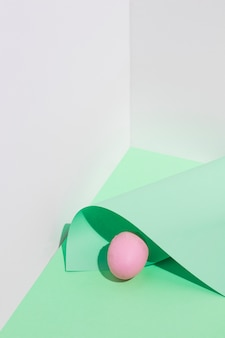 Small pink easter egg with paper sheet on table