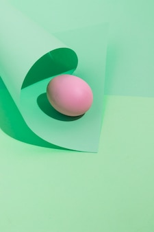 Small pink easter egg with rolled paper on table