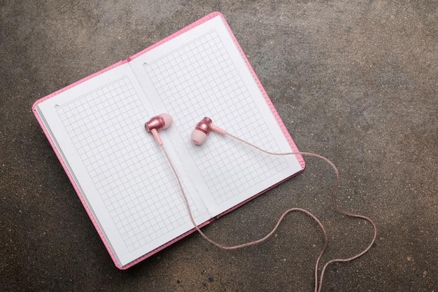 스마트폰용 작은 분홍색 헤드폰과 어두운 배경에 분홍색 노트북. 평면도.