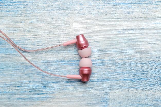 밝은 파란색 나무 배경에 작은 분홍색 헤드폰. 위에서 보기