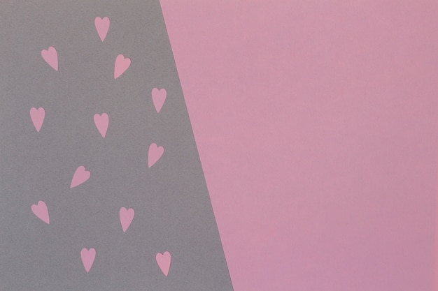 Small pink paper cut hearts on gray and pink background with copy space