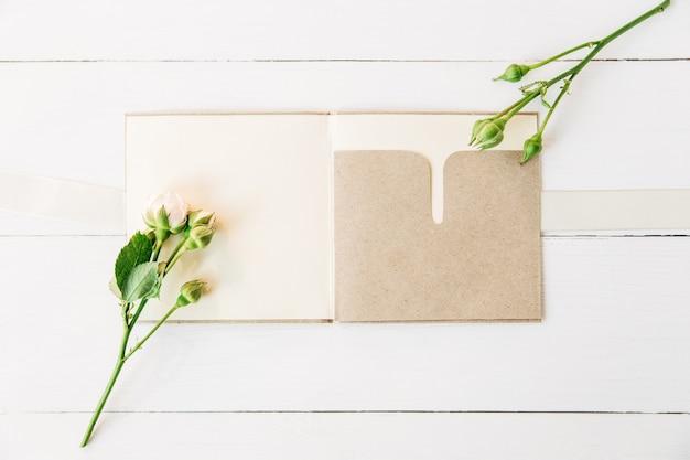 공예 종이 열린 봉투가 있는 작은 분홍색 장미최소한의 평평한 평지 흰색 나무 배경
