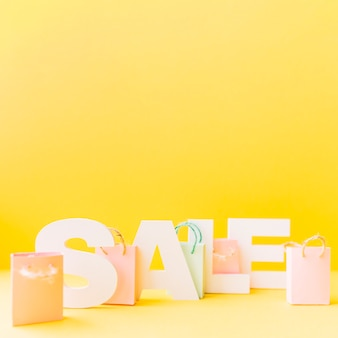 Small pink shopping bag in front of letter sale on yellow background