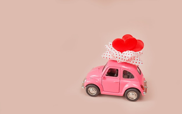 Small pink toy car with a gift bow and hearts on the roof against a pink background. delivery of gifts for valentine's day, world women's day.