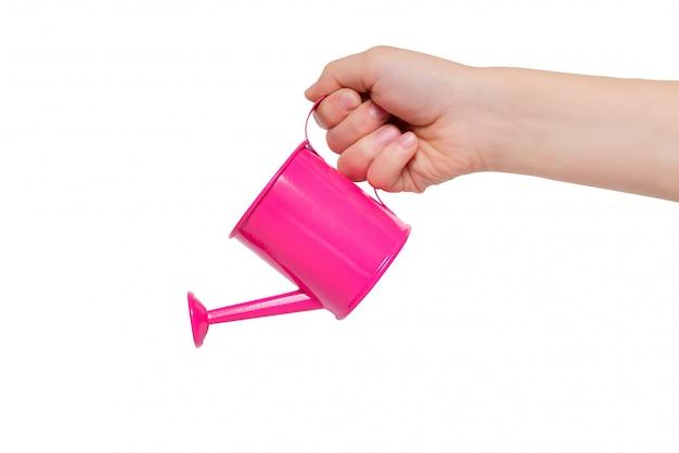 分離された子供の手で小さなピンクのじょうろ