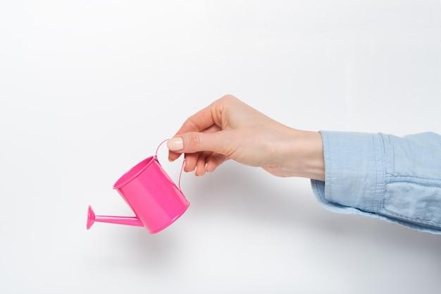 光に女性の手で小さなピンクのじょうろ