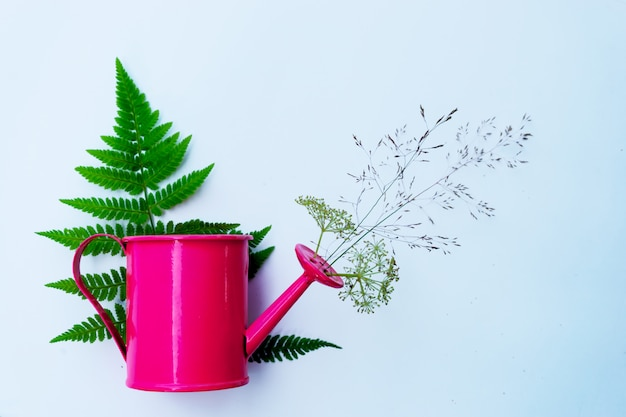 A small pink watering can is decorated with wildflowers and herbs. the concept of gardening and country mood.
