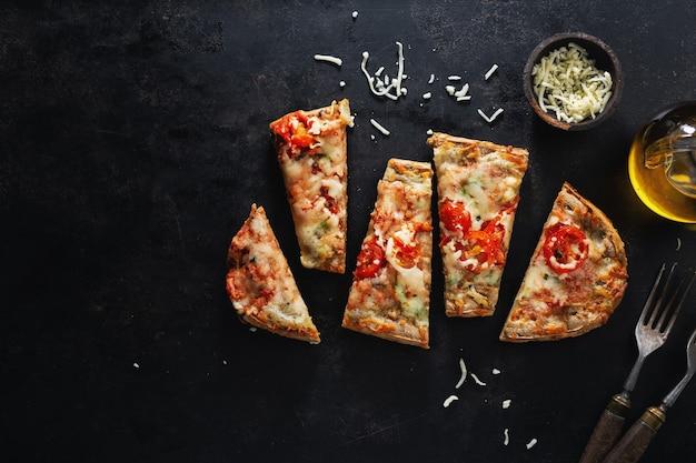 暗い背景にチーズと小さなピザの作品。上からの眺め。
