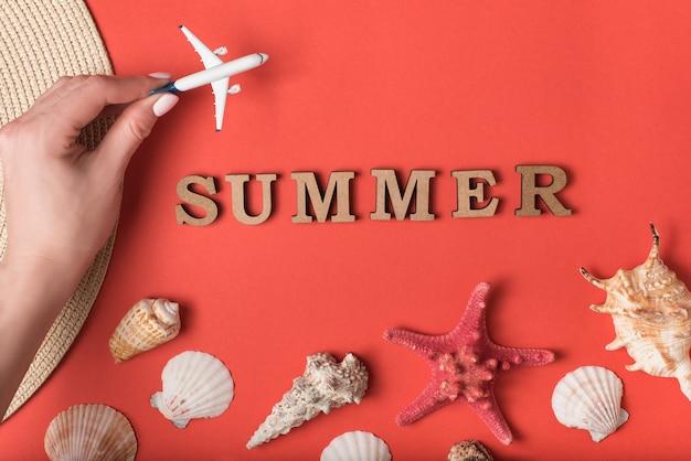 女性の手の中の小さな飛行機。木製の手紙から単語夏。貝殻、ヒトデ、生きたサンゴの空間。休暇の概念