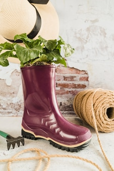 Small plant planted in the purple wellington rubber boot with spool of rope; hat and garden fork against weathered wall