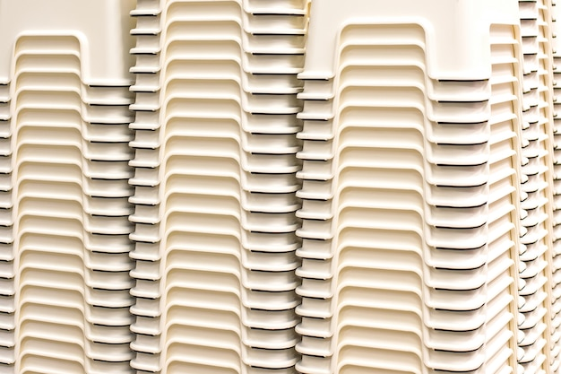 Small plastic chairs stacked in multiple layers.