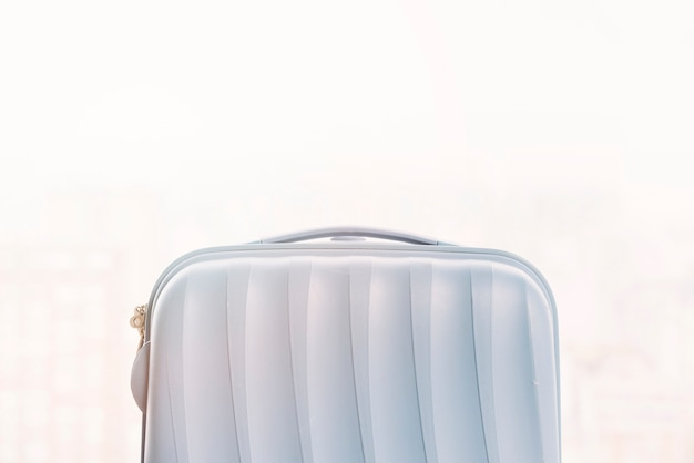 Small plastic luggage bag against white background