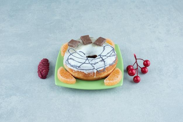Маленькая тарелка с пончиком и мармеладом рядом с рождественскими украшениями на мраморе.