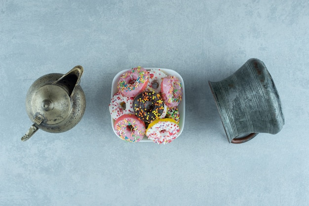 주전자와 대리석 주전자 사이의 작은 도넛 접시.